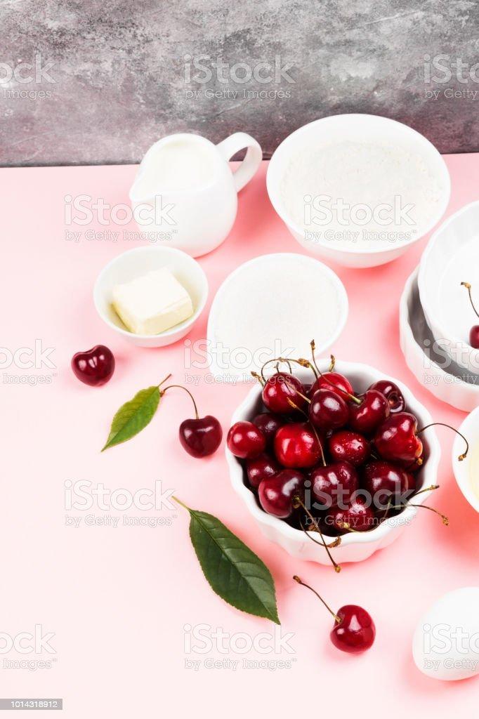 Ingredientes para torta de cereja - leite, manteiga, ovos, farinha, cereja, açúcar em um fundo rosa. Copie o espaço. Fundo de alimentos - foto de acervo