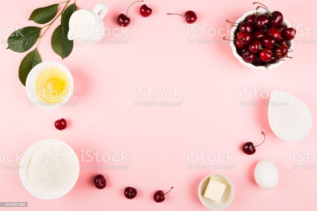 Ingredientes para torta de cereja - leite, manteiga, ovos, farinha, cereja, açúcar em um fundo rosa. Vista superior, copie o espaço. Fundo de alimentos - foto de acervo