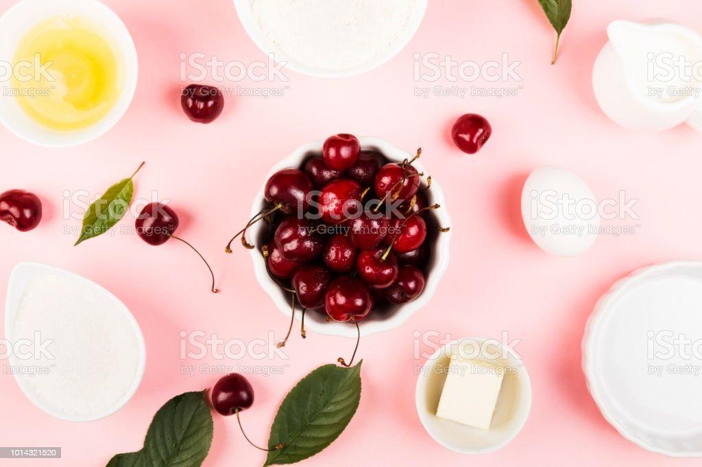 Ingredientes para torta de cereja - leite, manteiga, ovos, farinha, cereja, açúcar em um fundo rosa. Vista superior. Fundo de alimentos - foto de acervo