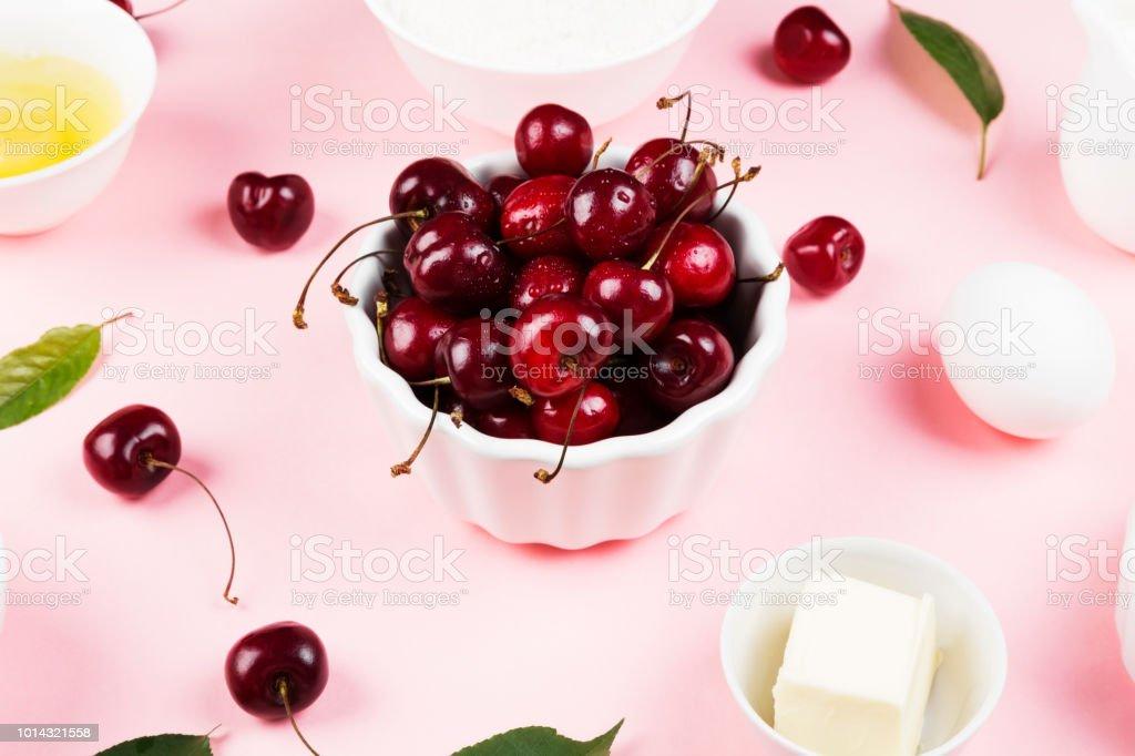 Ingredientes para torta de cereja - leite, manteiga, ovos, farinha, cereja, açúcar em um fundo rosa - foto de acervo