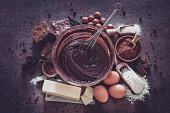 Top view of dark kitchen table filled with ingredients for preparing homemade chocolate brownies. The composition is arranged at the center of the frame. A large mixing bowl filled with chocolate spread mix and a wire whisk is at the center and all around it are other ingredients like butter, powdered cocoa, sugar, flour, eggs, chocolate bars salt and hazelnuts. Retro style processing. Predominant color is brown. Low key DSRL studio photo taken with Canon EOS 5D Mk II and Canon EF 100mm f/2.8L Macro IS USM.