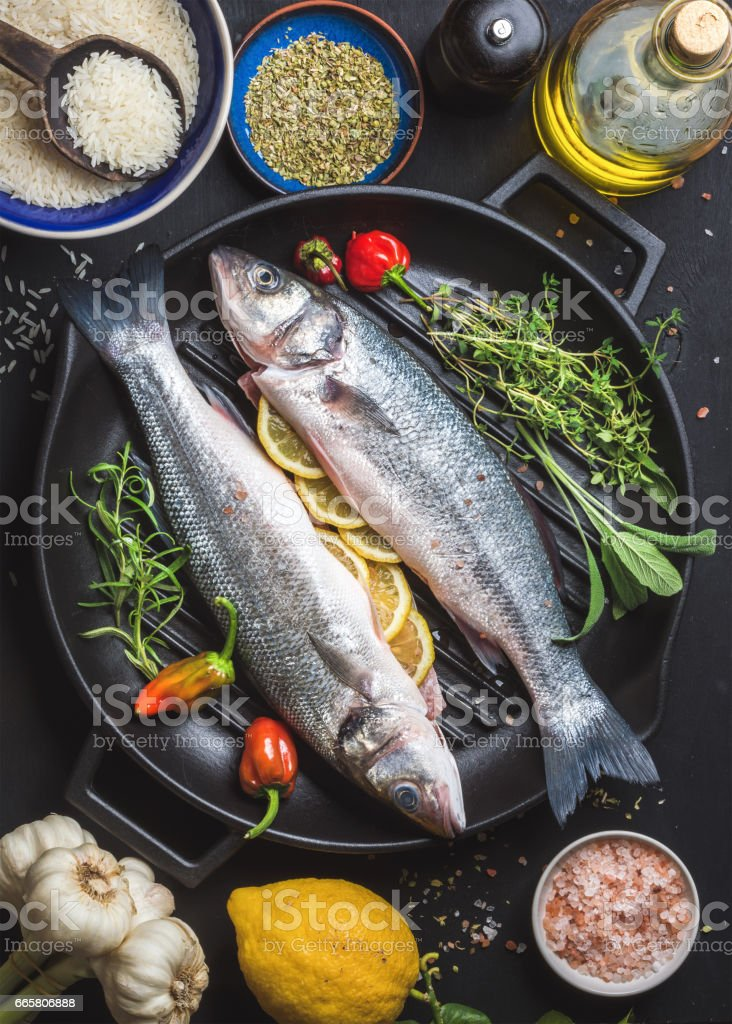 Ingredients for cookig healthy fish dinner. Raw uncooked seabass with rice, lemon, olive oil, herbs and spices on black grilling iron pan over dark background stock photo