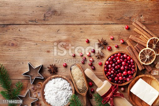 istock Ingredients for cooking Christmas baking. Flour, sugar, butter, cranberry and spices on kitchen wooden table top view. Bakery background. 1174640228