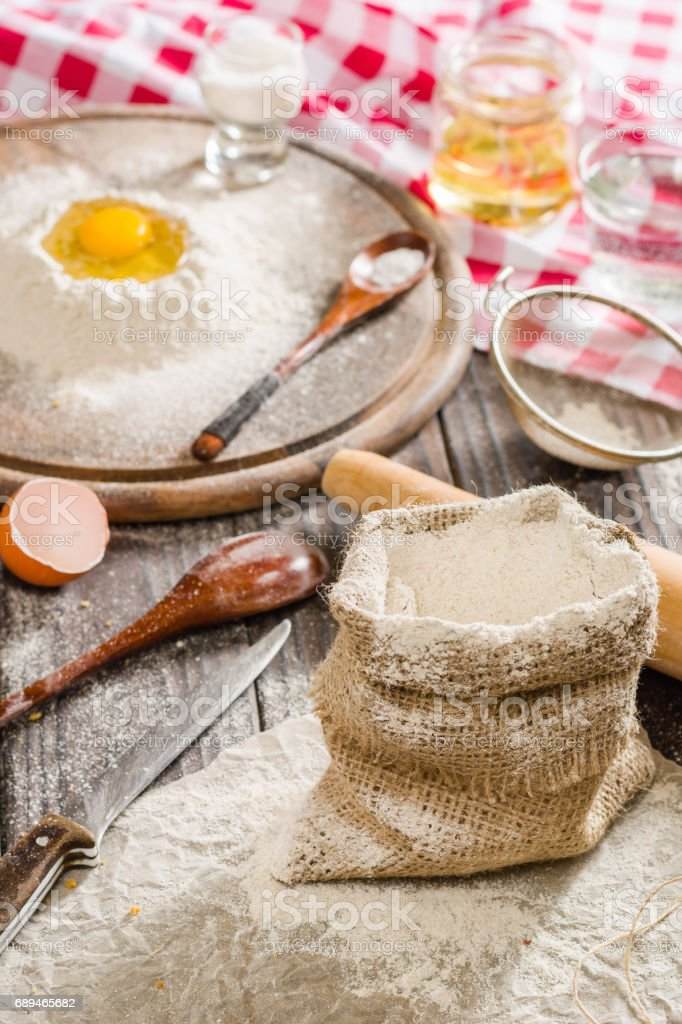 Ingredients for cooking dough or bread. Broken egg on top of a bunch of white rye flour. Dark wooden background. stock photo