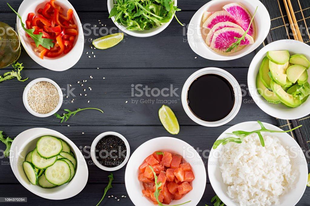 Zutaten für das Kochen hawaiianischen Lachs Fisch Poke Schüssel mit Reis, Avocado, Paprika, Gurken, Rettich, Sesam und Kalk. Buddha-Schüssel. Diätkost. Ansicht von oben – Foto
