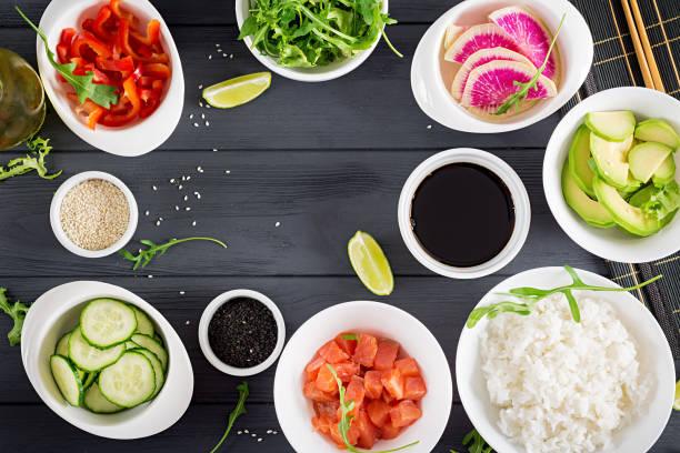 zutaten für das kochen hawaiianischen lachs fisch poke schüssel mit reis, avocado, paprika, gurken, rettich, sesam und kalk. buddha-schüssel. diätkost. ansicht von oben - hawaiianischer salat stock-fotos und bilder
