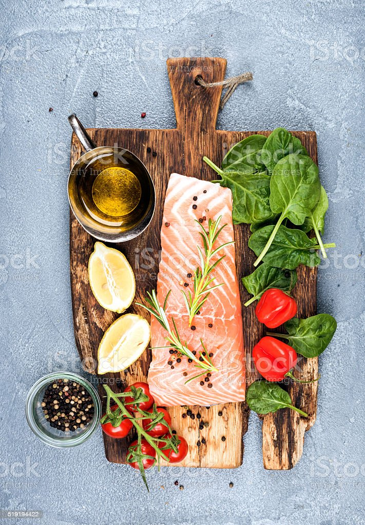 Ingredients for cooking healthy dinner. Raw salmon fillet, spinach, tomatoes stock photo