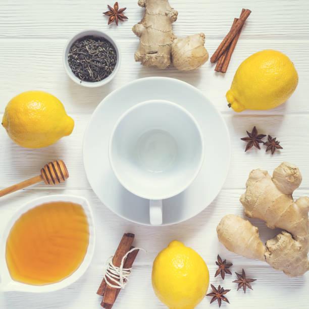 zutaten für das kochen gesunde natürliche heißgetränk. zitronen, honig, ingwer und zimt in eine leere tasse - immunsystem stärken stock-fotos und bilder