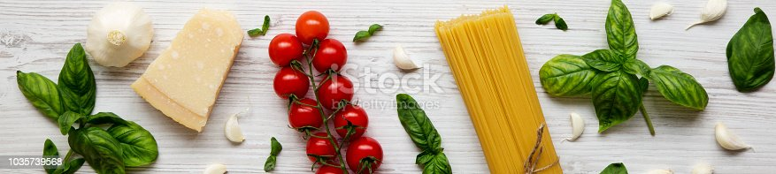 istock Ingredients for cooking italian pasta on a white wooden background. Flat lay. Top view. 1035739568
