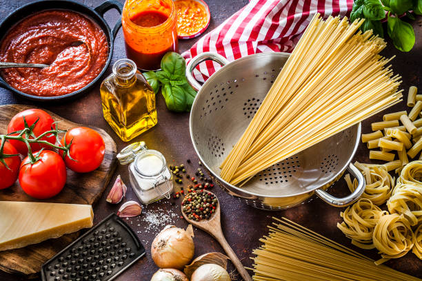 Ingredients for cooking Italian pasta High angle view of ingredients for cooking Italian pasta shot on dark kitchen table. Ingredients included in the composition are: spaghetti, olive oil, garlic, tomatoes, basil, Parmesan cheese, onion, salt and black pepper. The spaghetti are in a stainless steel colander. A glass jar and a cast iron pan filled with tomato sauce complete the composition. DSRL studio photo taken with Canon EOS 5D Mk II and Canon EF 100mm f/2.8L Macro IS USM uncooked pasta stock pictures, royalty-free photos & images