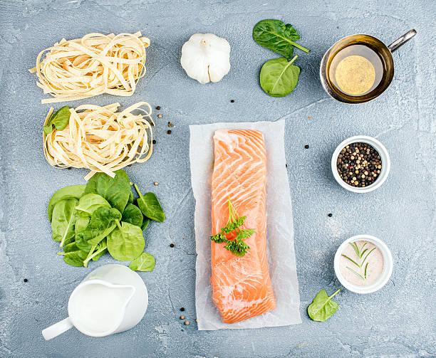 zutaten zum kochen nudeln tagliatelle mit räucherlachs, spinat und creme - spaghetti mit lachs stock-fotos und bilder