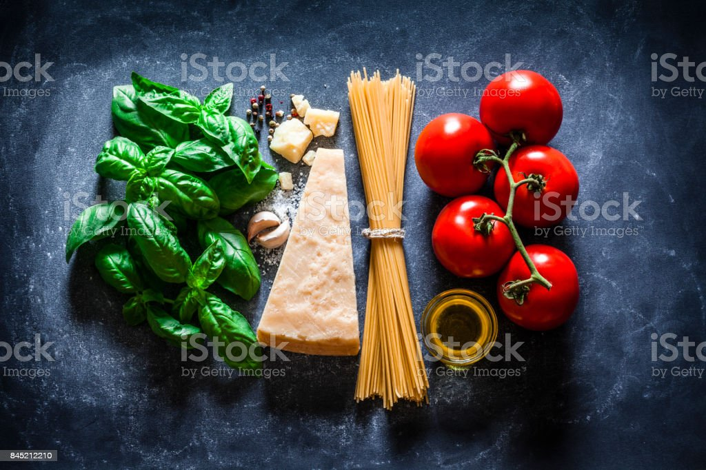 Ingredients for cooking traditional Italian spaghetti on dark background stock photo