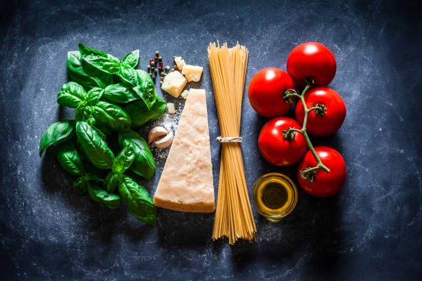 ingredients for cooking traditional italian spaghetti on dark background - italian food stock photos and pictures