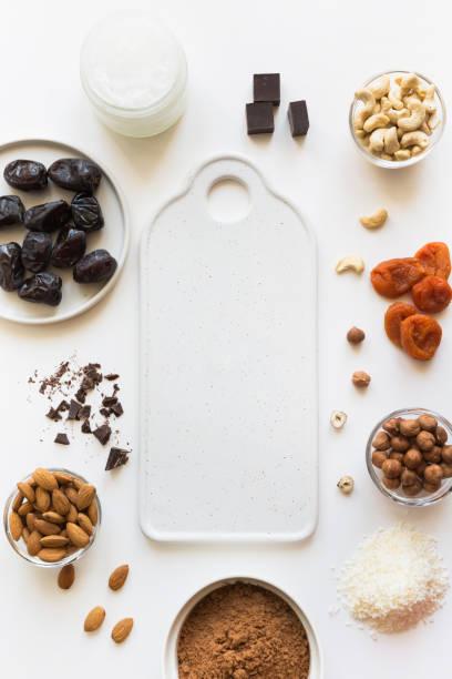 zutaten für energiedaten kugeln mit kakao und nüssen auf weiß. gesundes essen für veganer und kinder. - zuckerfreie lebensmittel stock-fotos und bilder