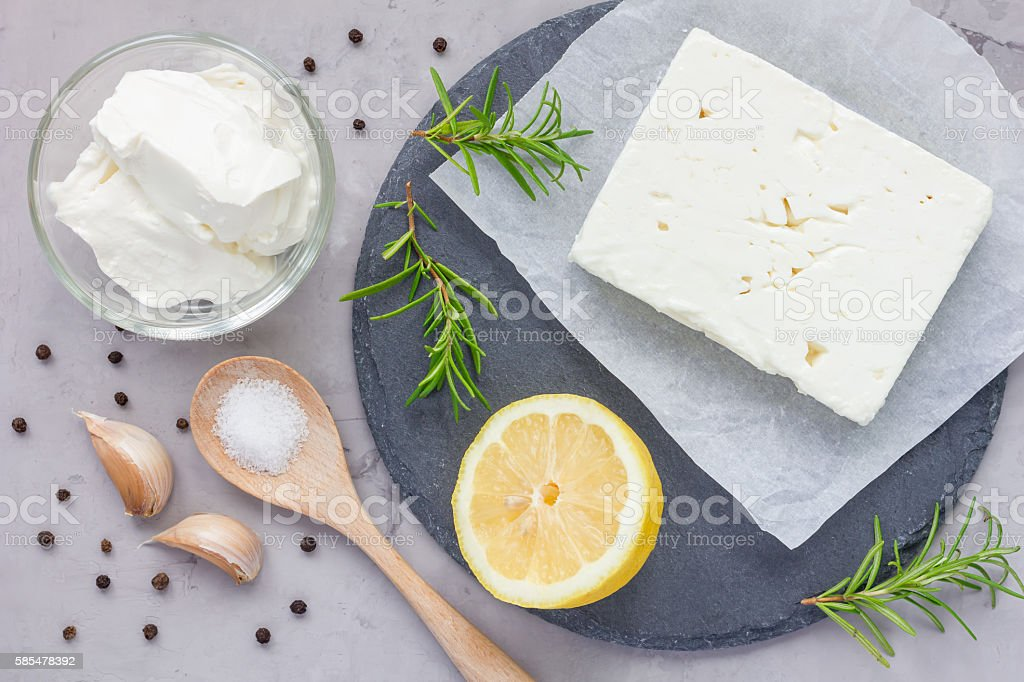 Ingredients for feta, cream cheese, rosemary, lemon and garlic dip stock photo