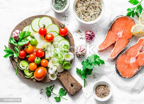 istock Ingredients for  healthy, balanced lunch - salmon and vegetables. Red fish, zucchini, squash, cherry tomatoes, leek, wild rice, spices on a light background, top view. Flat lay 1020682046