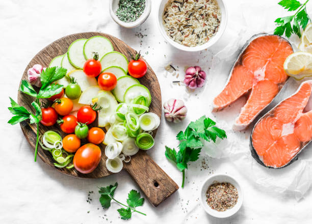 ingredients for  healthy, balanced lunch - salmon and vegetables. red fish, zucchini, squash, cherry tomatoes, leek, wild rice, spices on a light background, top view. flat lay - mediterranean food imagens e fotografias de stock