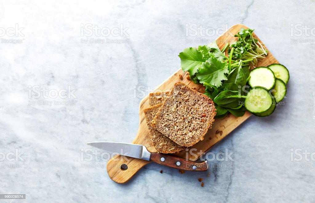 Ingredients for healthy home made sandwiches. Rye bread, spinach, young kale, cucumber, radish sprouts. Healthy eating concept. Flat lay stock photo