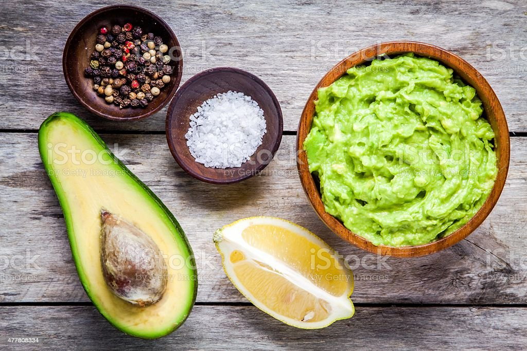ingredients for homemade guacamole: avocado, lemon, salt and pepper stock photo