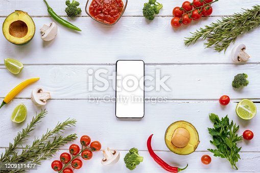1136817041 istock photo Ingredients for Italian cuisine and smartphone with blank screen in the center. 1209111477