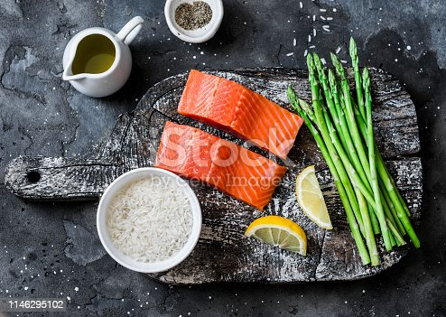 istock Ingredients for lunch - fresh raw organic salmon, green asparagus and rice on a dark background, top view 1146295102