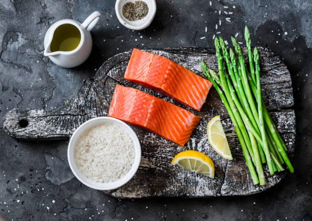 Zutaten zum Mittagessen-frischer roher Bio-Lachs, grüner Spargel und Reis auf dunklem Hintergrund, Top-Ansicht – Foto