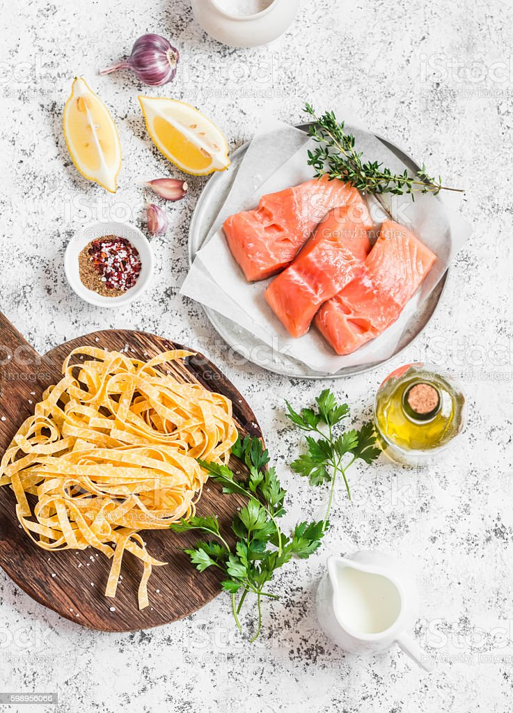 Ingredients for lunch - salmon, pasta, cream, olive oil, spices stock photo