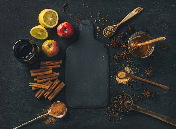 ingredients for making mulled wine over blue painted plywood background - karanfil baharat stok fotoğraflar ve resimler