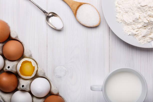 zutaten für die herstellung von pfannkuchen teig (eiern, mehl, milch, zucker, salz) auf weißer holztisch. ansicht von oben. kopieren sie raum. - backrahmen stock-fotos und bilder
