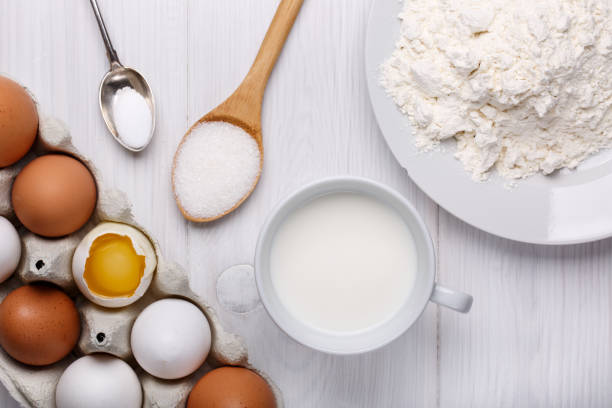 Ingredients for making pancake dough (eggs, flour, milk, sugar, salt) on white wooden table. Top view. stock photo