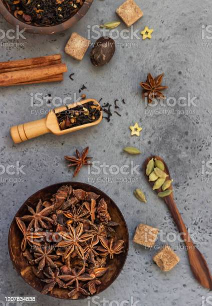 Photo of Ingredients for making spicy Indian masala chai tea or coffee. Dried black tea, roasted coffee beans, dry anise star seeds, cinnamon sticks, cardamom, black pepper and brown sugar.