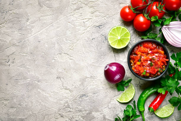Ingredients for making tomato salsa (salsa roja) - traditional mexican sauce Ingredients for making tomato salsa (salsa roja) - traditional mexican sauce on a grey slate,stone or concrete background.Top view with copy space. salsa sauce stock pictures, royalty-free photos & images