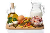 Ingredients for pasta, macaroni,pepper, garlic, olive oil,  parsley,milk,bacon on wooden background