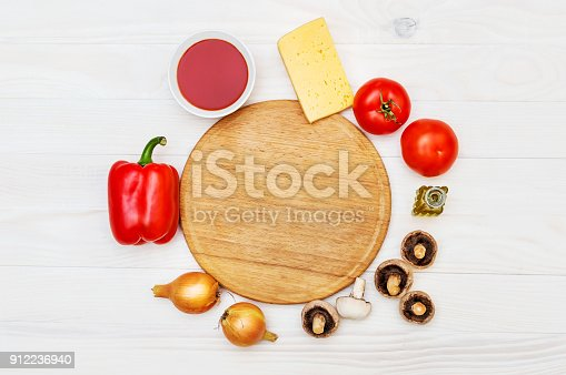 istock Ingredients for pizza with cutting board on the white wooden table. Cooking pizza concept. Top view. Copy space. 912236940