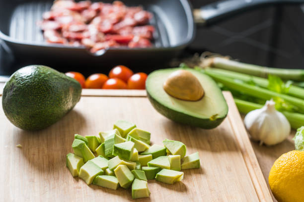 Ingredients for preparation of salad with pork, avocado, tomato, garlic and celery. stock photo