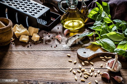 High angle view of various ingredients for preparing pesto sauce like basil, garlic, parmesan cheese, olive oil, salt, pepper and pine nuts on a wooden backdrop. predominant colors are green and brown. Low key DSLR photo taken with Canon EOS 6D Mark II and Canon EF 24-105 mm f/4L