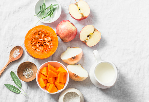istock Ingredients for pumpkin apple soup on white background, top view. Pumpkin, apples, cream, onion, sage - ingredients for a healthy lunch 869767096