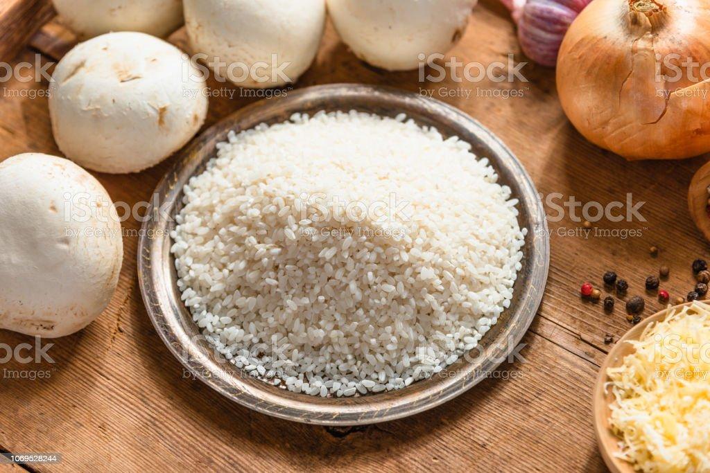 Ingredientes para risoto - arroz, cogumelos, cebola, alho e queijo ralado - foto de acervo