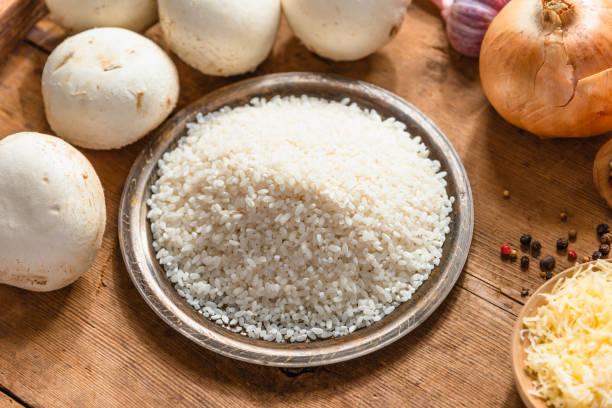 ingredientes para risoto - arroz, cogumelos, cebola, alho e queijo ralado - fine dining - fotografias e filmes do acervo