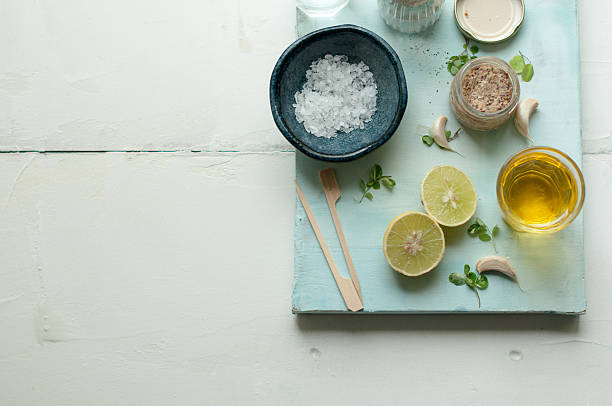 Ingredients for salad dressing on a white and blue background with lemon, olive oil, sea salt, mustard, pepper and garlic vinaigrette dressing stock pictures, royalty-free photos & images