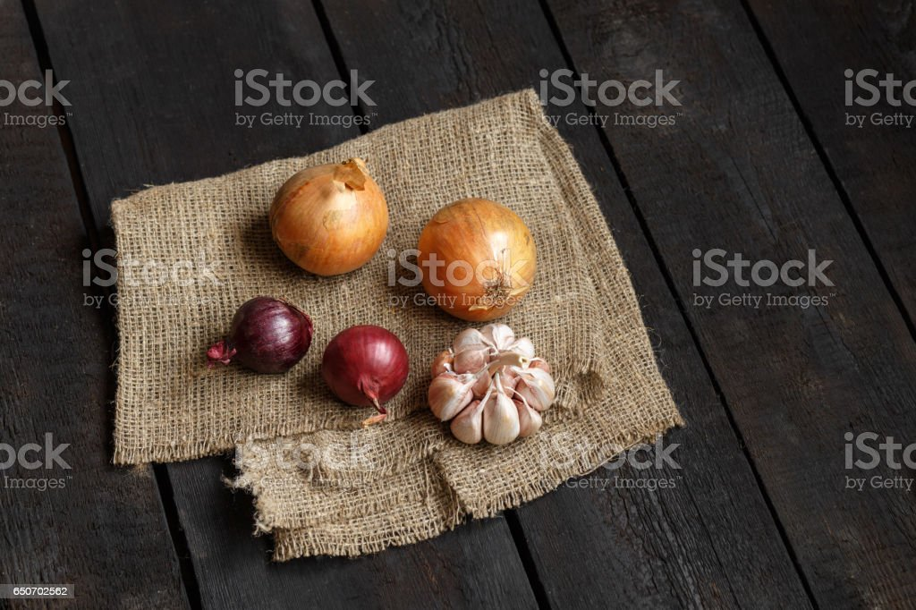 Ingredients for soup or salad: onion, garlic on a dark background stock photo