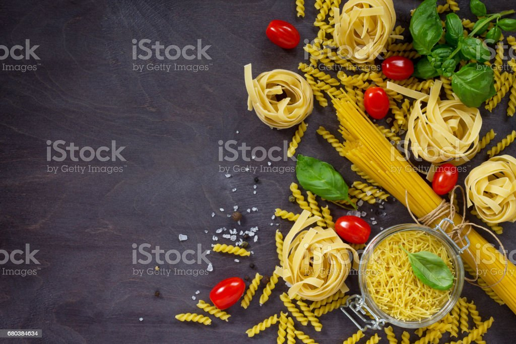 Ingredients for the preparation of Italian pasta - spaghetti, fusilli, fettuccine, basil, cherry tomato and pepper. Top view with space for text. royalty-free stock photo