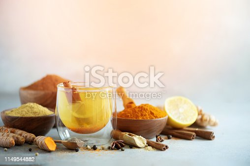 Ingredients for turmeric hot tea on grey background. Healthy ayurvedic drink with lemon, ginger, cinnamon, turmeric. Immune boosting remedy.