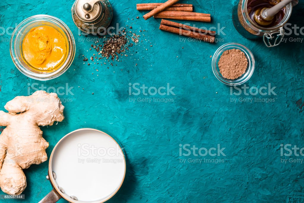 Ingredients for turmeric latte  on cyan background top view stock photo