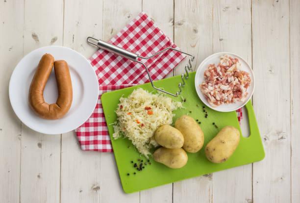 ingrediënten voor een typisch nederlands gerecht zuurkool met zuurkool, gerookte worst, spek en aardappelen - stamppot stockfoto's en -beelden