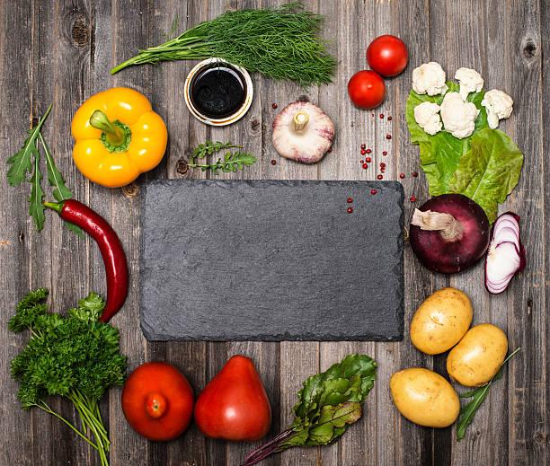 Ingredients for vegetarian cooking around slate board. – Foto
