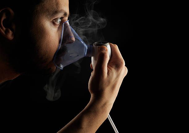 Inhalation therapy profile on black background Inhalation therapy on black background. Smooth sidelight and mist clearly visible. respiratory disease stock pictures, royalty-free photos & images