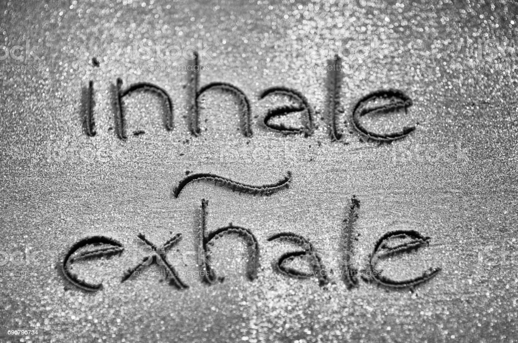Inhale Exhale Handwritten in Sand stock photo