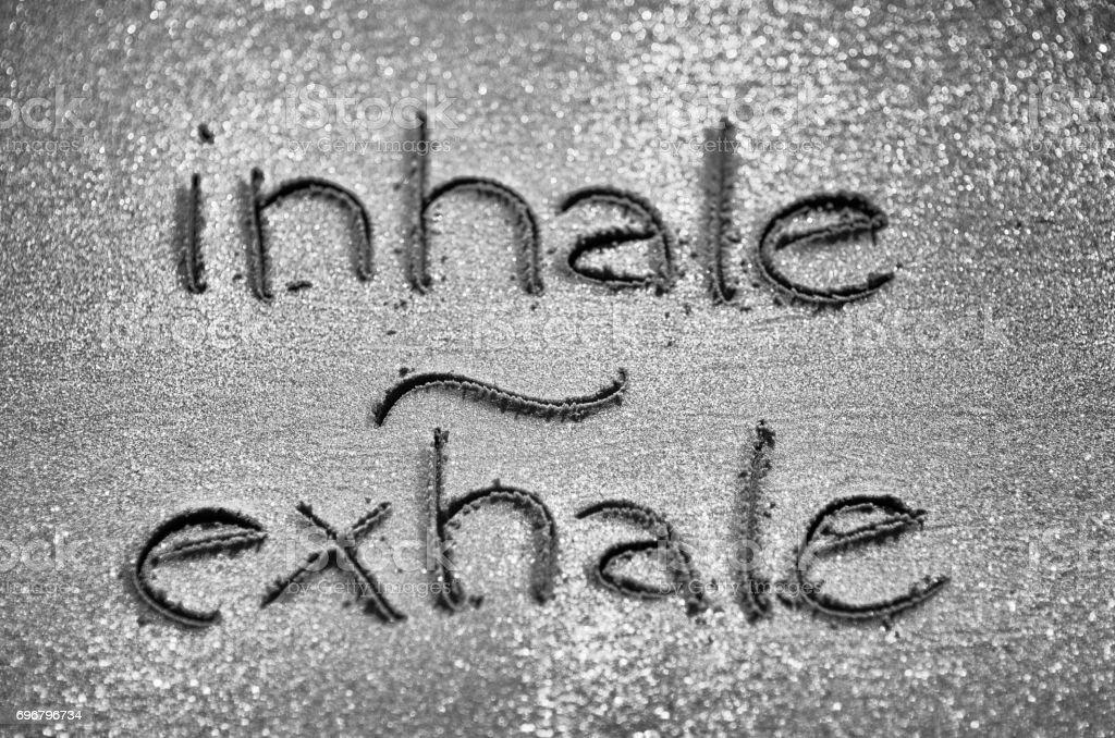 Inhaleren Exhale handgeschreven in zand foto