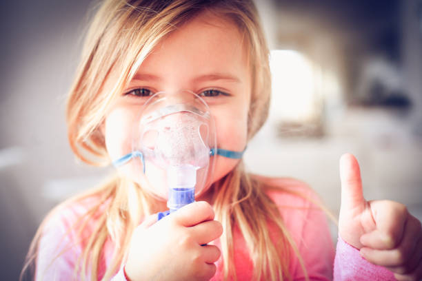 Inhaler. Smiling little girl using inhaler and showing OK. oxygen mask stock pictures, royalty-free photos & images